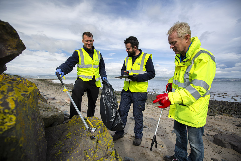 Wastewater team collecting, recording and bagging marine litter at Craigavad